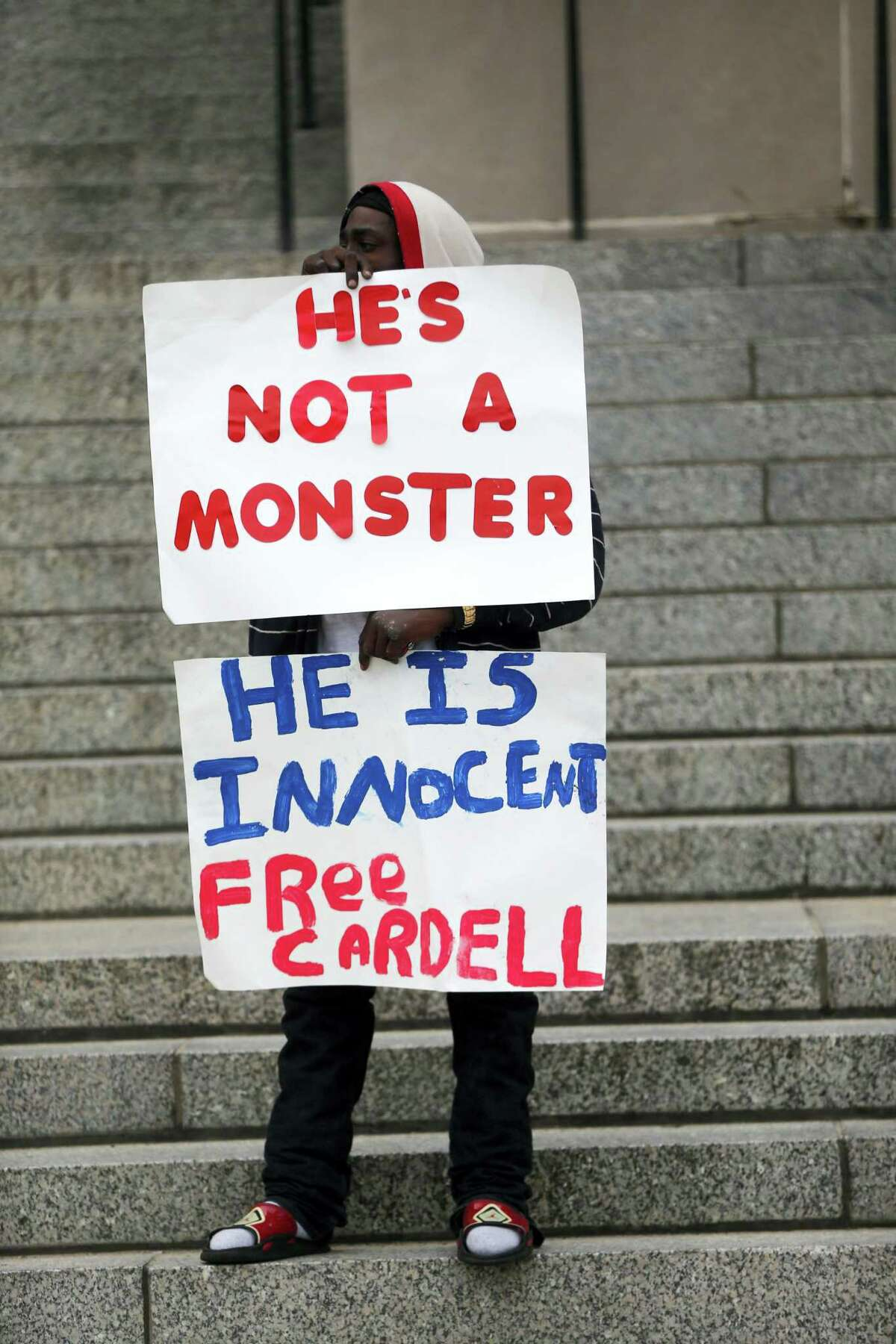 A supporter of Cardell Hayes holds signs outside Orleans Parish Criminal District Court, during a break in Hayes' murder trial in New Orleans, Wednesday, Dec. 7, 2016. Hayes killed former NFL New Orleans Saints player Will Smith in a road rage incident, in which Smith's wife, Racquel Smith was also shot and wounded.
