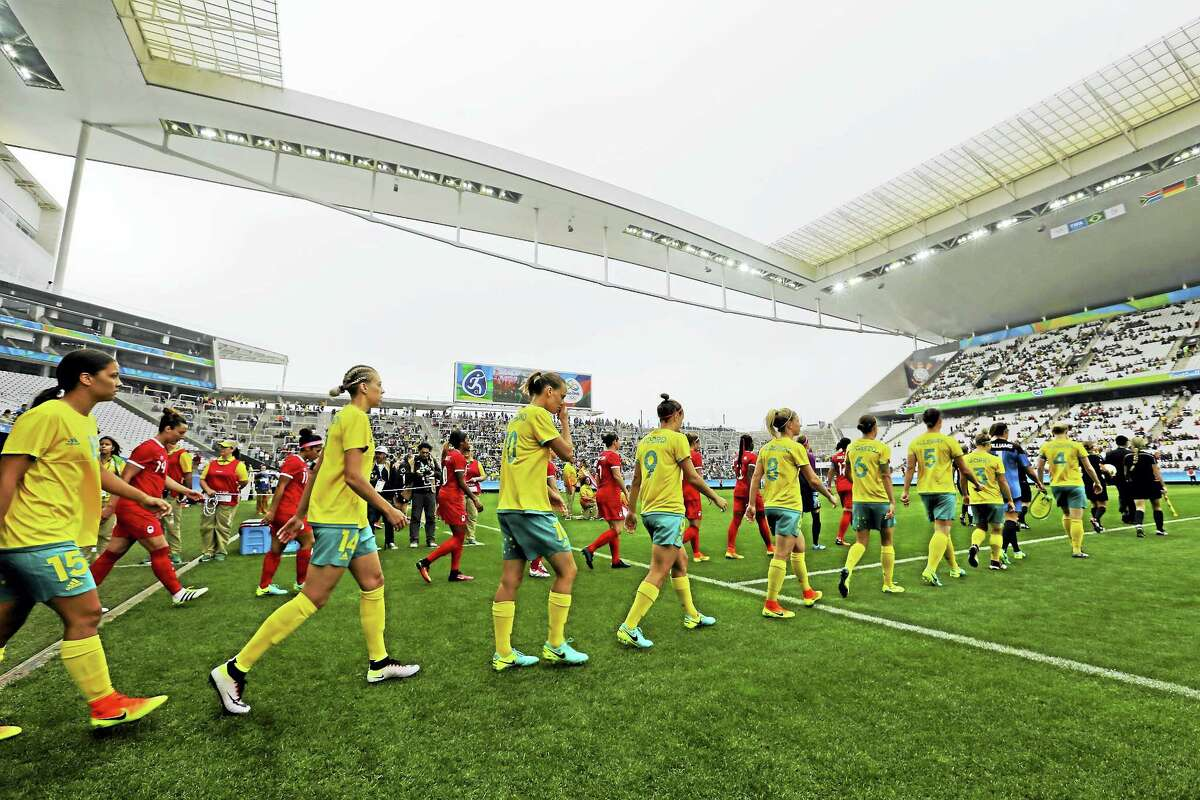 Australia, front row, and Canada soccer players step onto the pitch Wednesday before their 2016 Summer Olympics match at the Arena Corinthians in Sao Paulo, Brazil, the first action at the Games.