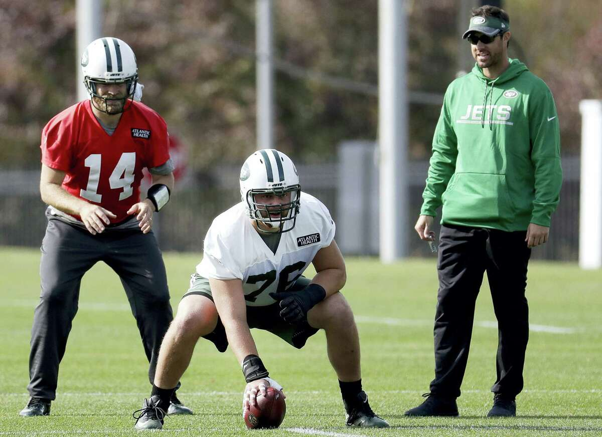 Ryan Fitzpatrick, left, prepares for the snap from center Wesley Johnson during a practice in Florham Park, N.J.