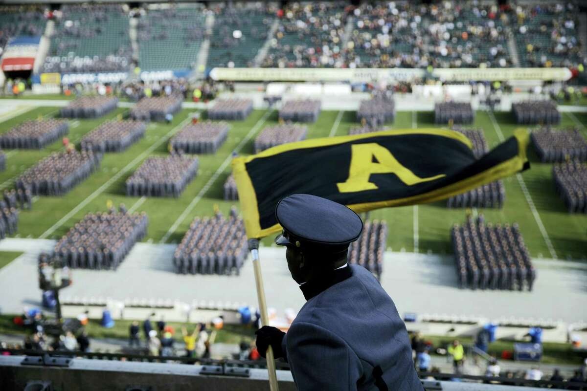 An Army Cadet signals Cadets as they march onto the field before a game against Navy in Philadelphia.