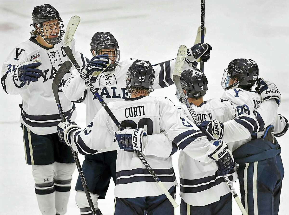 Members of the Yale hockey team celebrate after Joe Snively (7) scored in the second period against Rensselaer on Friday night at Ingalls Rink.