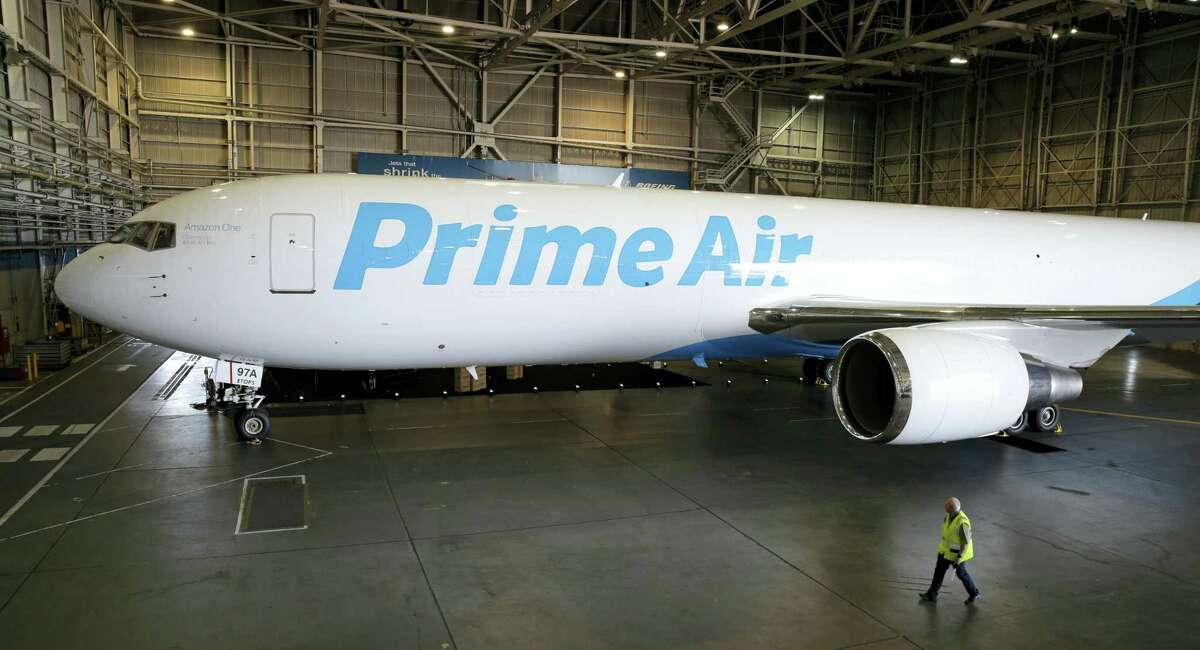 """A worker walks past a Boeing 767 with an Amazon.com """"Prime Air"""" livery on display Thursday in a Boeing hangar in Seattle."""