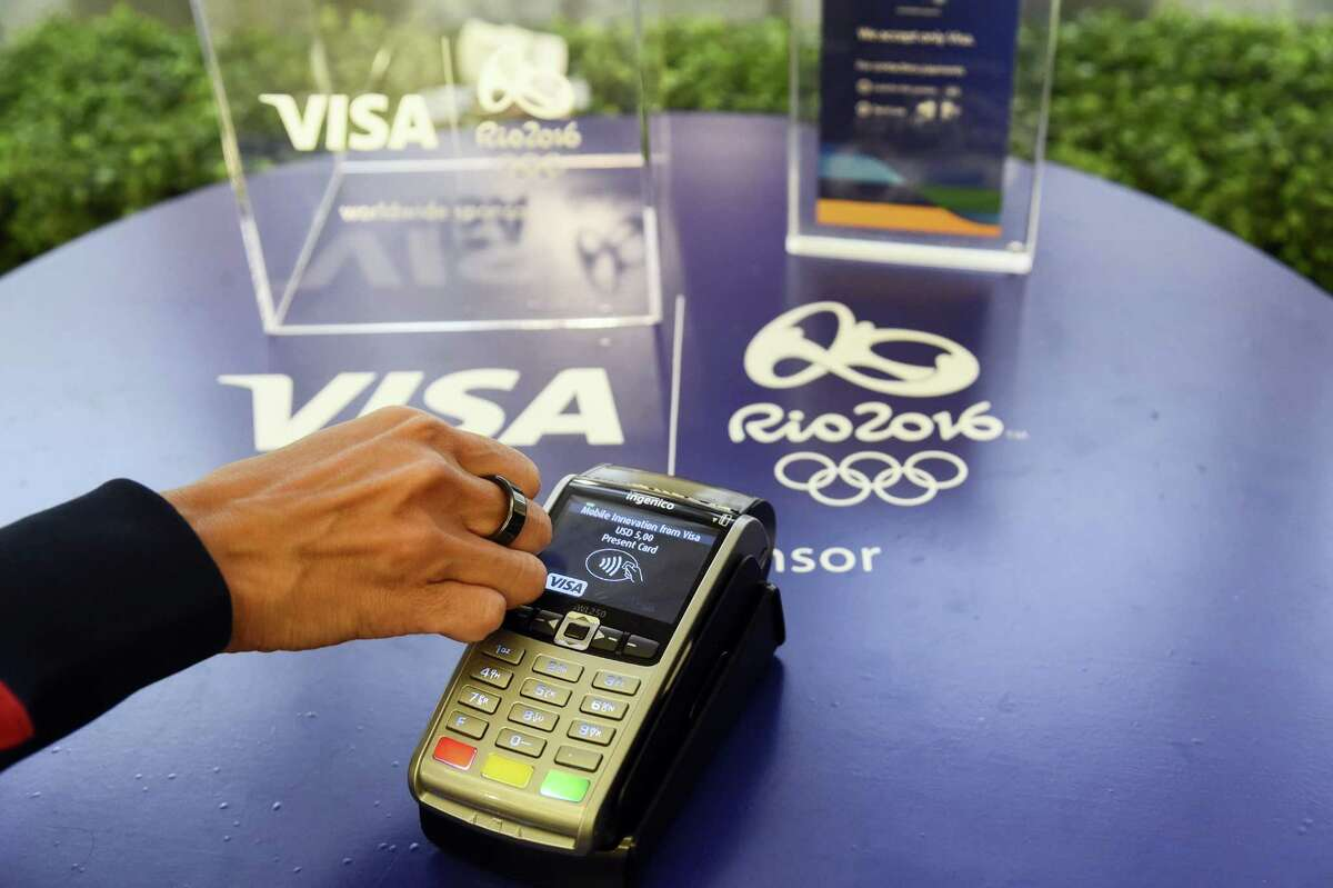 This June 2, 2016 photo shows a Visa payment ring near a payment terminal in New York. Visa, a 30-year Olympics sponsor, is the official payment provider of the Olympics, providing payment infrastructure for the games themselves.