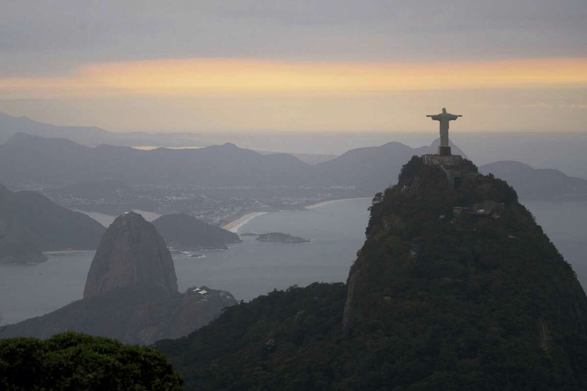 The Christ the Redeemer statue and Sugar Loaf mountain stand as the sun rises in Rio de Janeiro, Brazil, on Thursday.