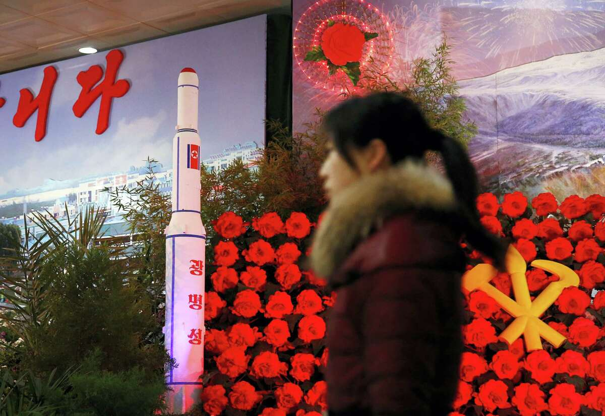 """In this Feb. 15, 2016, file photo, a visitor at a flower festival walks past a model of North Korea's newest satellite Kwangmyongsong 4 on display as part of celebrations, a day before the 74th birthday anniversary, also known as the """"Day of the Shining Star,"""" of late North Korean leader Kim Jong Il in Pyongyang, North Korea. North Korean space officials are hard at work on a five-year plan that they say will put more satellites into orbit and lay the groundwork for a shot to the moon."""