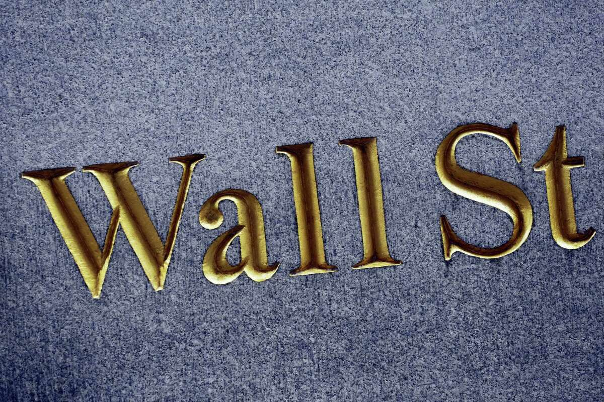 This photo shows a sign for Wall Street carved into the side of a building, in New York.
