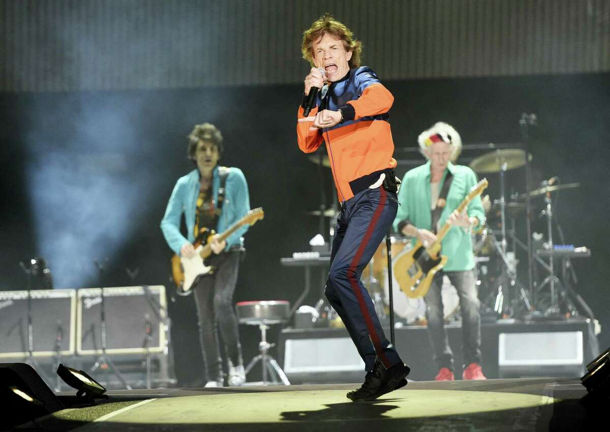 In this Oct. 7, 2016 photo, Mick Jagger, center, performs with Ron Wood, left, and Keith Richards of the Rolling Stones during their performance on day 1 of the 2016 Desert Trip music festival at Empire Polo Field in Indio, Calif. Jagger, the 73-year-old frontman of the Rolling Stones, was on hand Dec. 8, 2016 at a New York hospital when girlfriend, Melanie Hamrick, gave birth to the couple's son.