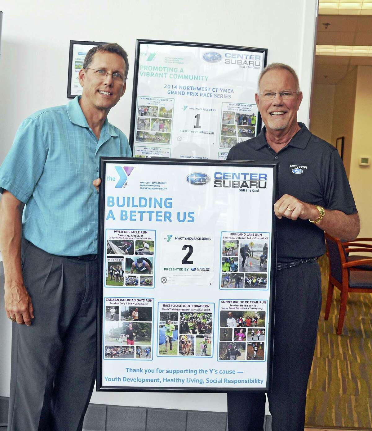 """Contributed photo Northwest CT YMCA CEO Greg Brisco, left, presented a special gift to Center Subaru owner Phil Porter, right, July 28 at the dealership on Winsted Road in Torrington. The Y has been chosen as the dealership's Hometown Charity for its annual """"Share the Love"""" campaign the past three years. In total, Center Subaru has donated $94,000 to the Y through the campaign - money put toward providing financial aid to assure that all children and families can participate and benefit in the Y's programs and services. The framed picture highlights the races in the Y's 2015 Grand Prix Race Series in which Center Subaru was the presenting sponsor."""
