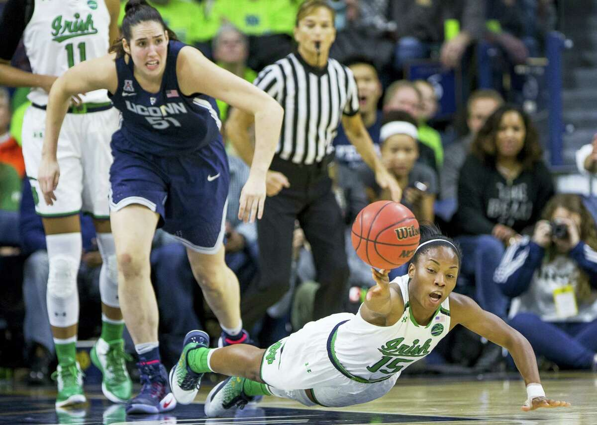 Notre Dame's Lindsay Allen (15) dives for a loose ball in front of UConn's Natalie Butler (51) during the first half of top-ranked UConn's 72-61 win over No. 2 Notre Dame Wednesday night in South Bend, Ind.