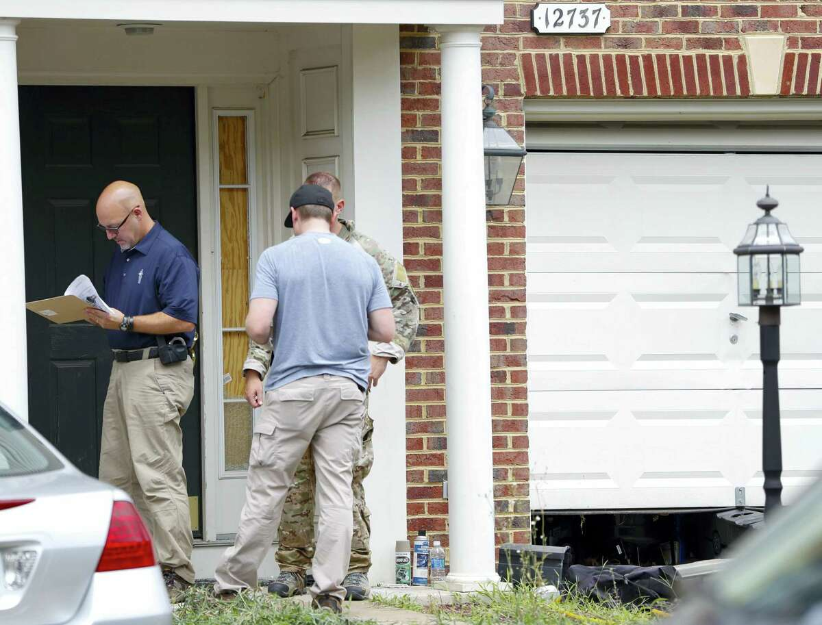 Law enforcement officers stand outside the home of Nicholas Young, a Washington Metro Transit Officer on Wednesday in Fairfax, Va. Young was arrested at Metro's headquarters in Washington and charged with a single count of attempting to provided material support to a terrorist group.