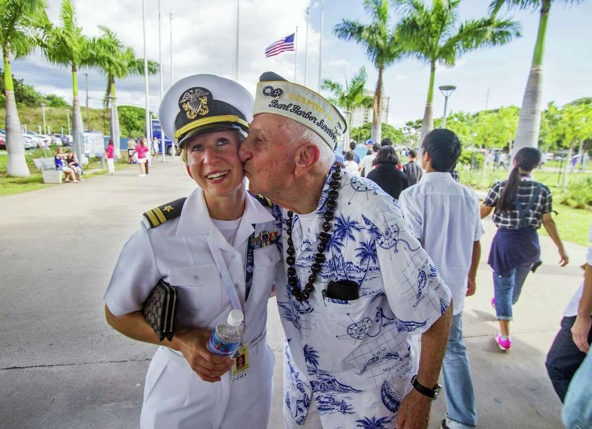 """In this Monday, Dec. 5, 2016, photo, about 30 Pearl Harbor Survivors with the """"Greatest Generation"""" vets meet and greet with visitors at the Pearl Harbor Visitor Center in Honolulu. Lt. Dawn Stankus, left, was there to help escort the Pearl Harbor survivors and Edward W. Stone, right, suddenly gave her a kiss and said, """"I hope you don't mind."""" Stankus replied, """"It was an honor to be kissed by you."""" On Wednesday, Dec. 7, thousands of servicemen and women and members of the public are expected to attend the 75th anniversary ceremony of the attack on Pearl Harbor that left more than 2,300 service people dead."""