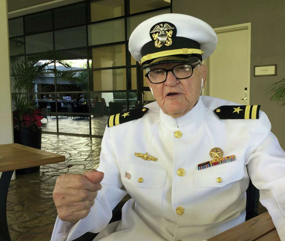 In this Monday, Dec. 5, 2016, photo, Jim Downing, wearing a Navy uniform, answers questions during an interview in Honolulu. Downing is among a few dozen survivors of the Japanese attack on Pearl Harbor who plan to gather at the Hawaii naval base, Wednesday, Dec. 7, 2016, to remember those killed 75 years ago. Thousands of servicemen and women and members of the public are also expected to attend the ceremony.