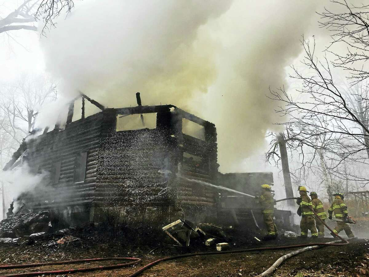 Ben Lambert - The Register CitizenFirefighters work to contain a fire at a house on Estey Road in Norfolk Wednesday morning.