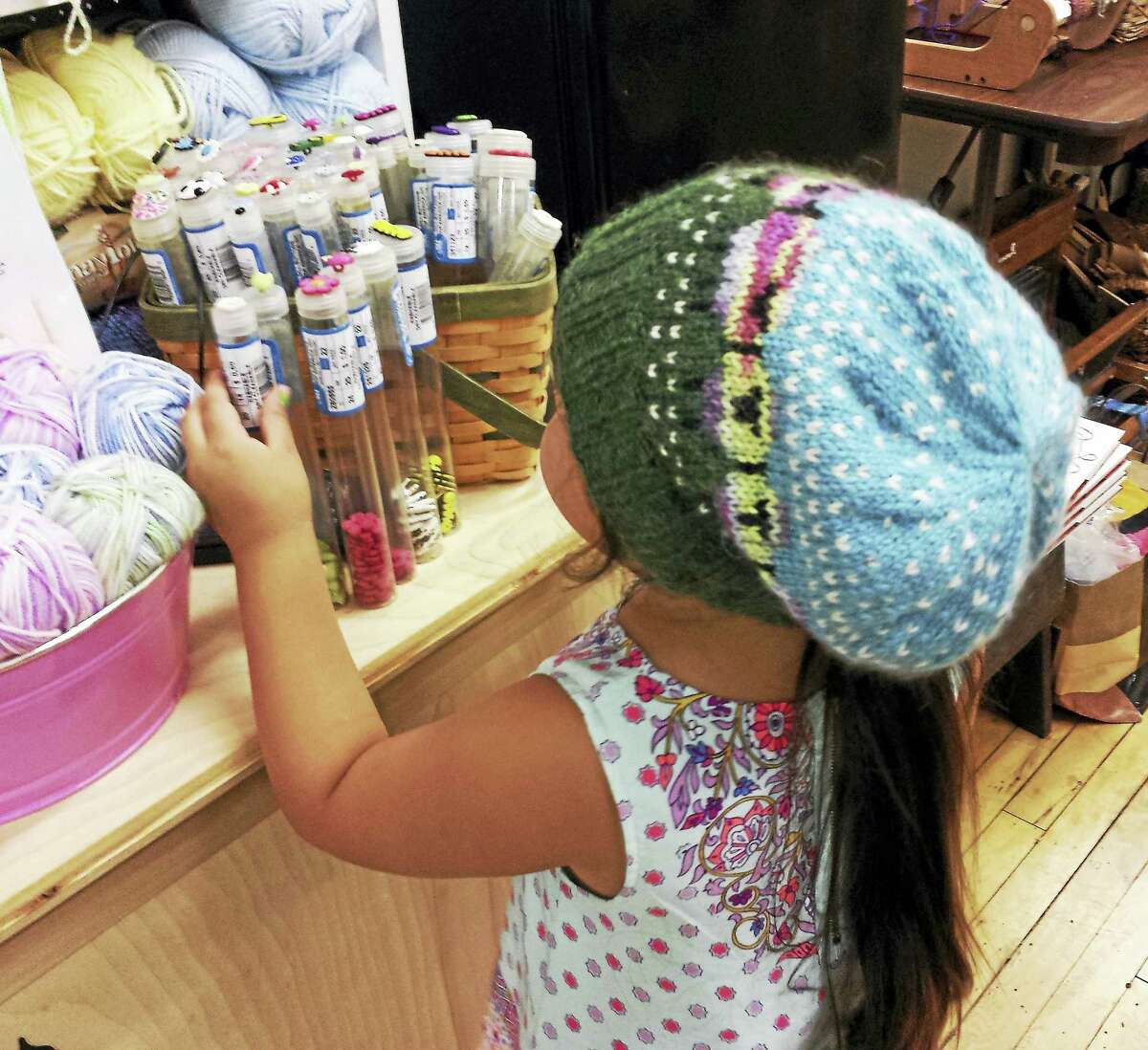 Photo by Ginger BalchGranddaughter Aariana wears a sheep hat while arranging buttons.