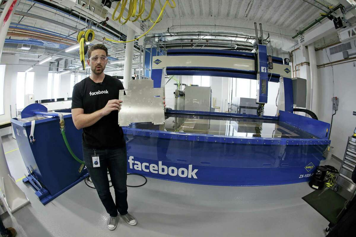In this photo taken Aug. 2, 2016, model maker Spencer Burns holds up a piece of sheet metal while standing in front of a water jet during a tour of Area 404, the hardware R&D lab, at Facebook headquarters in Menlo Park, Calif.