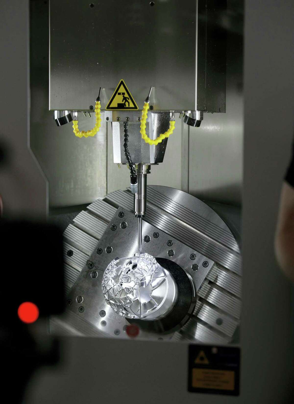 In this photo taken Aug. 2, 2016, a Facebook globe is made inside a 5 axis vertical milling machine in Area 404, the hardware R&D lab, at Facebook headquarters in Menlo Park, Calif.