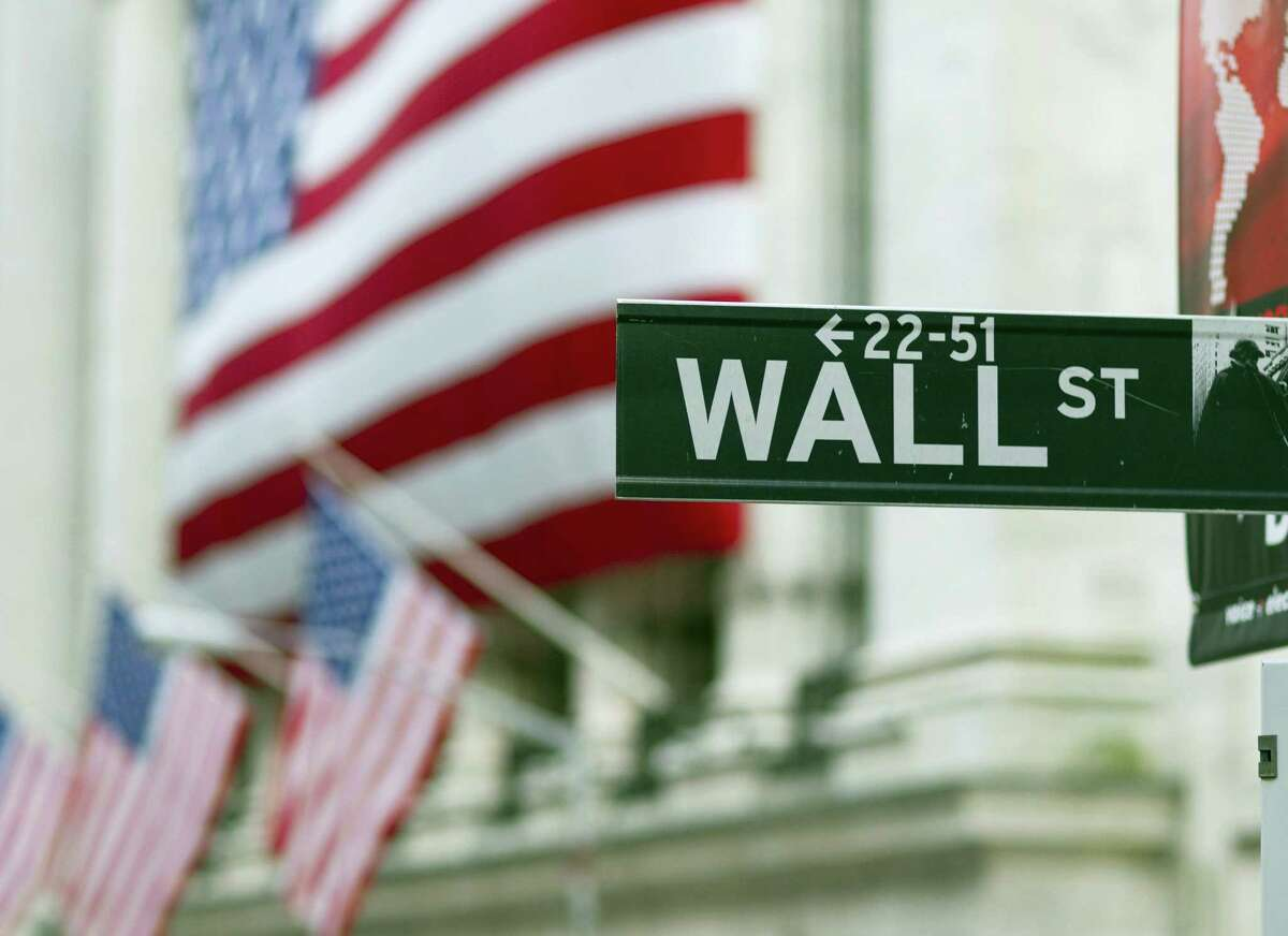 FILE - In this Aug. 8. 2011 file photo, a Wall Street sign hangs near the New York Stock Exchange, in New York. Stocks are opening slightly lower, Wednesday, Aug. 3, 2016, on Wall Street following sideways moves in Europe and Asia.