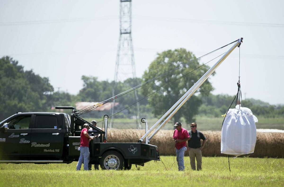 A crew hoists a bag holding the remains of a hot air balloon that crashed Saturday onto a waiting truck at the scene near Lockhart, Texas, Monday, Aug. 1, 2016. Sixteen people were killed in the incident.