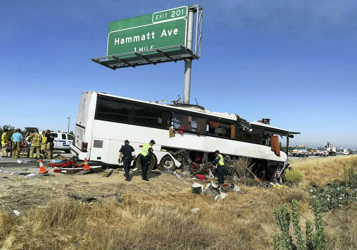 Authorities investigate the scene of a charter bus crash on northbound Highway 99 between Atwater and Livingston, Calif., Tuesday, Aug. 2, 2016. A charter bus veered off a central California freeway before dawn Tuesday and struck a pole that sliced the vehicle nearly in half, killing mulitple people and sending at least five others to hospitals, authorities said.