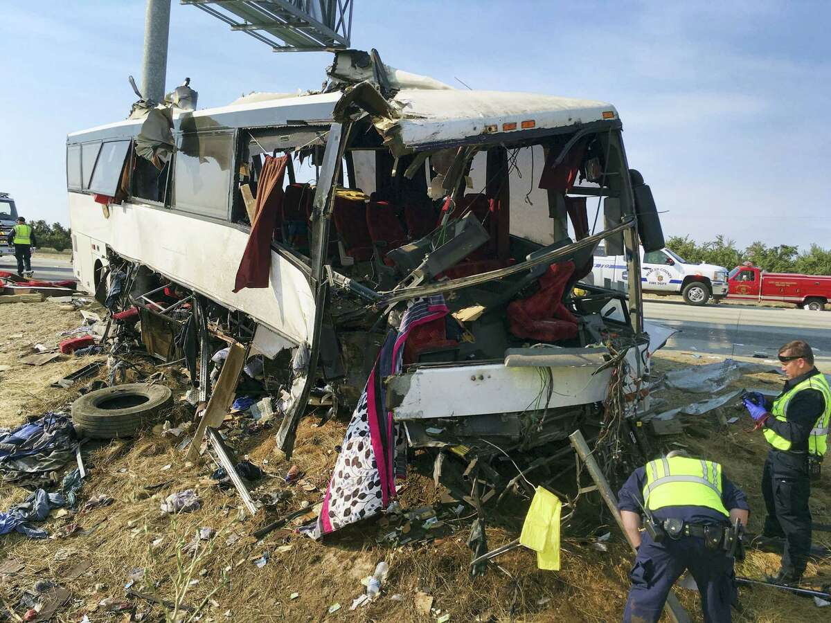 Authorities investigate the scene of a charter bus crash on northbound Highway 99 between Atwater and Livingston, Calif., Tuesday, Aug. 2, 2016. A charter bus veered off a central California freeway before dawn Tuesday and struck a pole that sliced the vehicle nearly in half, killing multiple people and sending at least five others to hospitals, authorities said. (AP Photo/Scott Smith)
