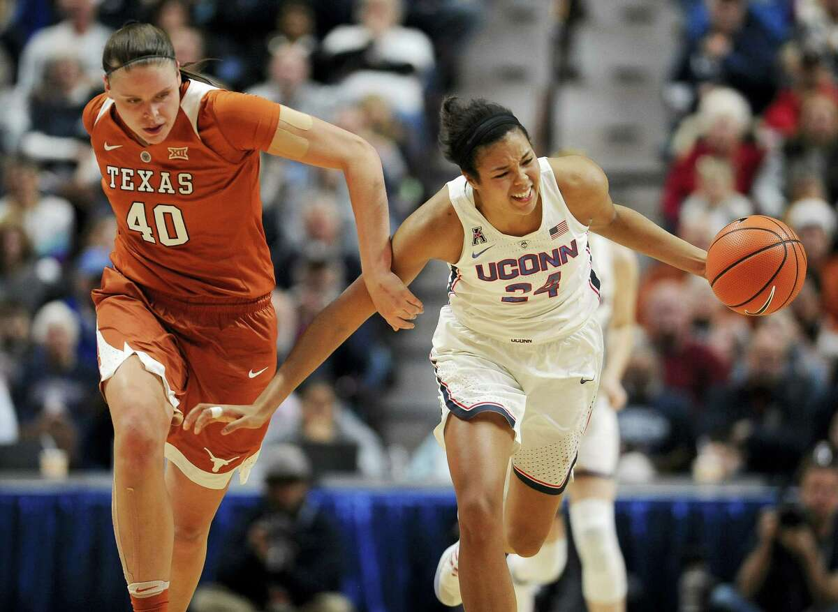 Connecticut's Napheesa Collier, right, is fouled as she steals the ball from Texas's Kelsey Lang, left, in the second half of an NCAA college basketball game Sunday, Dec. 4, 2016 in Uncasville, Conn.
