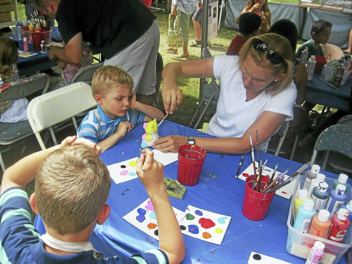 Photos by John Torsiello Chris Rettler helps her sons, Brady, left, and Lee, bottom, paint during a children's activity at the fair days.