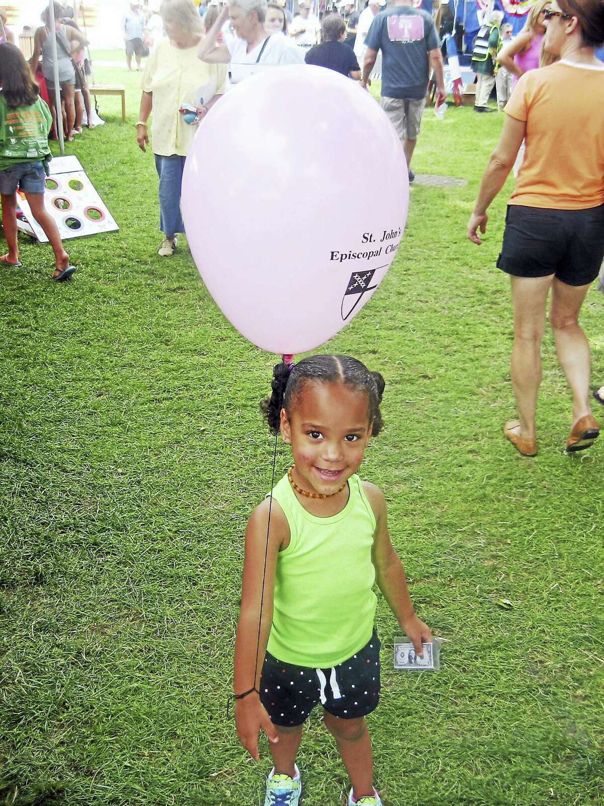 Photos by John Torsiello Little Olivia Allen holds a balloon during her visit to the New Milford Village Fair Days.