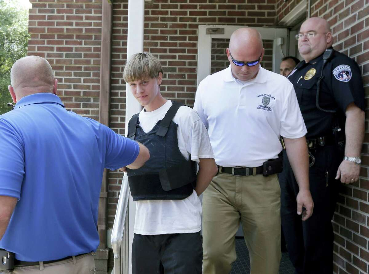 Charleston, S.C., shooting suspect Dylann Storm Roof, center, is escorted from the Sheby Police Department in Shelby, N.C. on June 18, 2015. Roof is a suspect in the shooting of several people Wednesday night at the historic The Emanuel African Methodist Episcopal Church in Charleston, S.C.