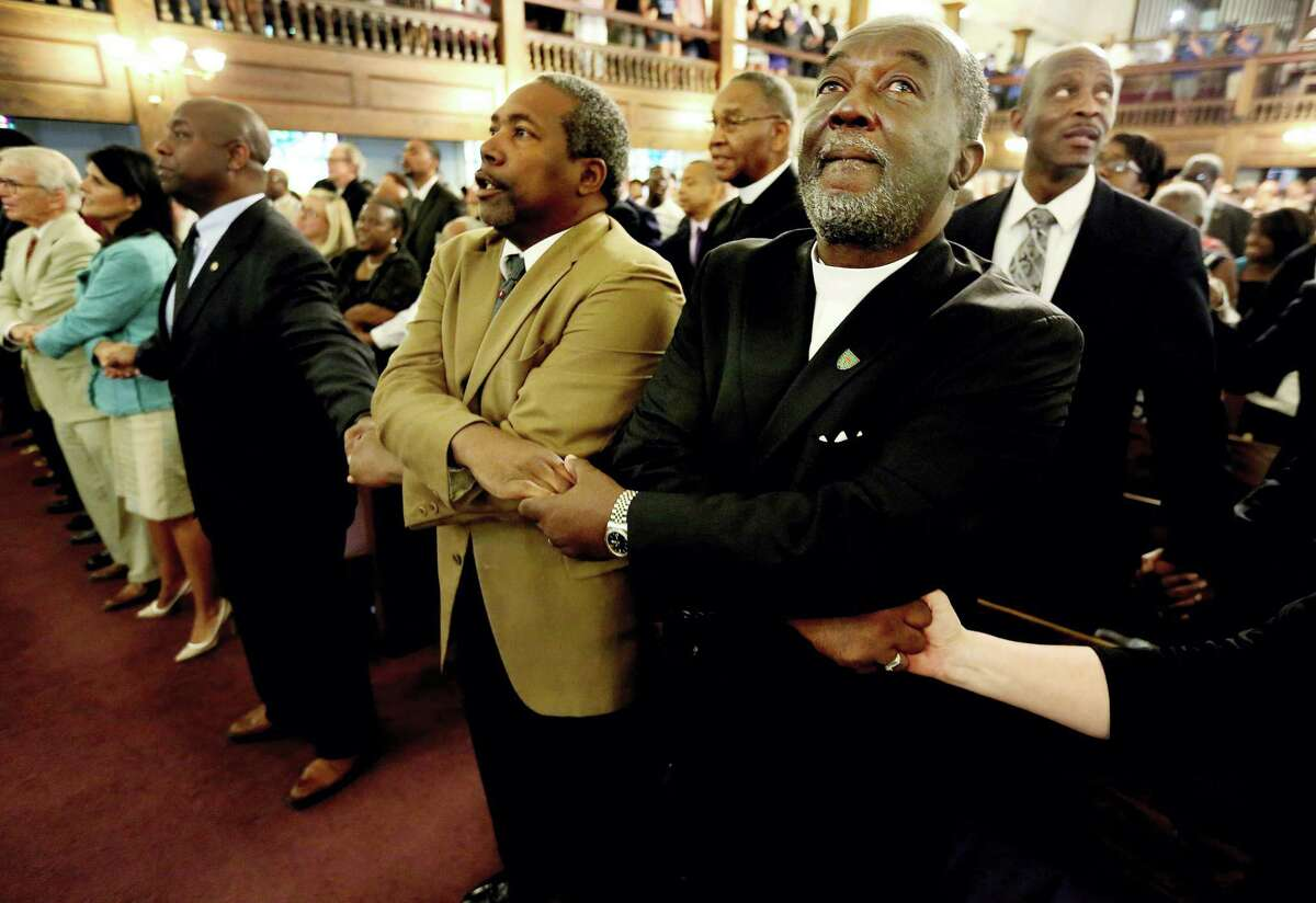 From left, Reverend Richard Harkness holds hands with Reverend Jack Lewin during a prayer vigil held at Morris Brown AME Church for the victims of Wednesday's shooting at Emanuel AME Church on June 18, 2015 in Charleston, S.C. Dylann Storm Roof, 21, was arrested Thursday in the slayings of several people, including the pastor at a prayer meeting inside the historic black church.