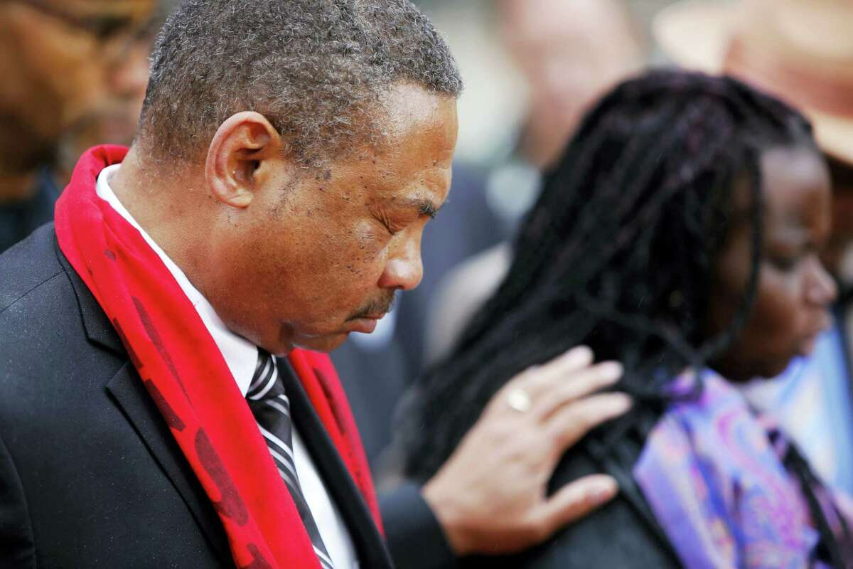 Pastor Thomas Dixon, left, prays during a prayer vigil in front of the Charleston County Courthouse as the jury deliberates in the Michael Slager trial Monday in Charleston, S.C. Slager, the former North Charleston police officer is charged with murder in the shooting death last year of Walter Scott.