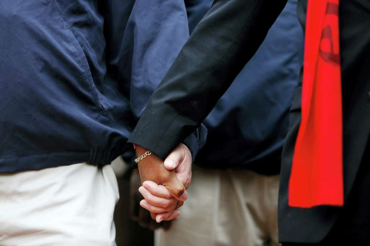 Pastors Rob Dewey, left, and Thomas Dixon hold hands during a prayer vigil in front of the Charleston County Courthouse as the jury deliberates in the Michael Slager trial Monday in Charleston, S.C. Slager, the former North Charleston police officer is charged with murder in the shooting death last year of Walter Scott.