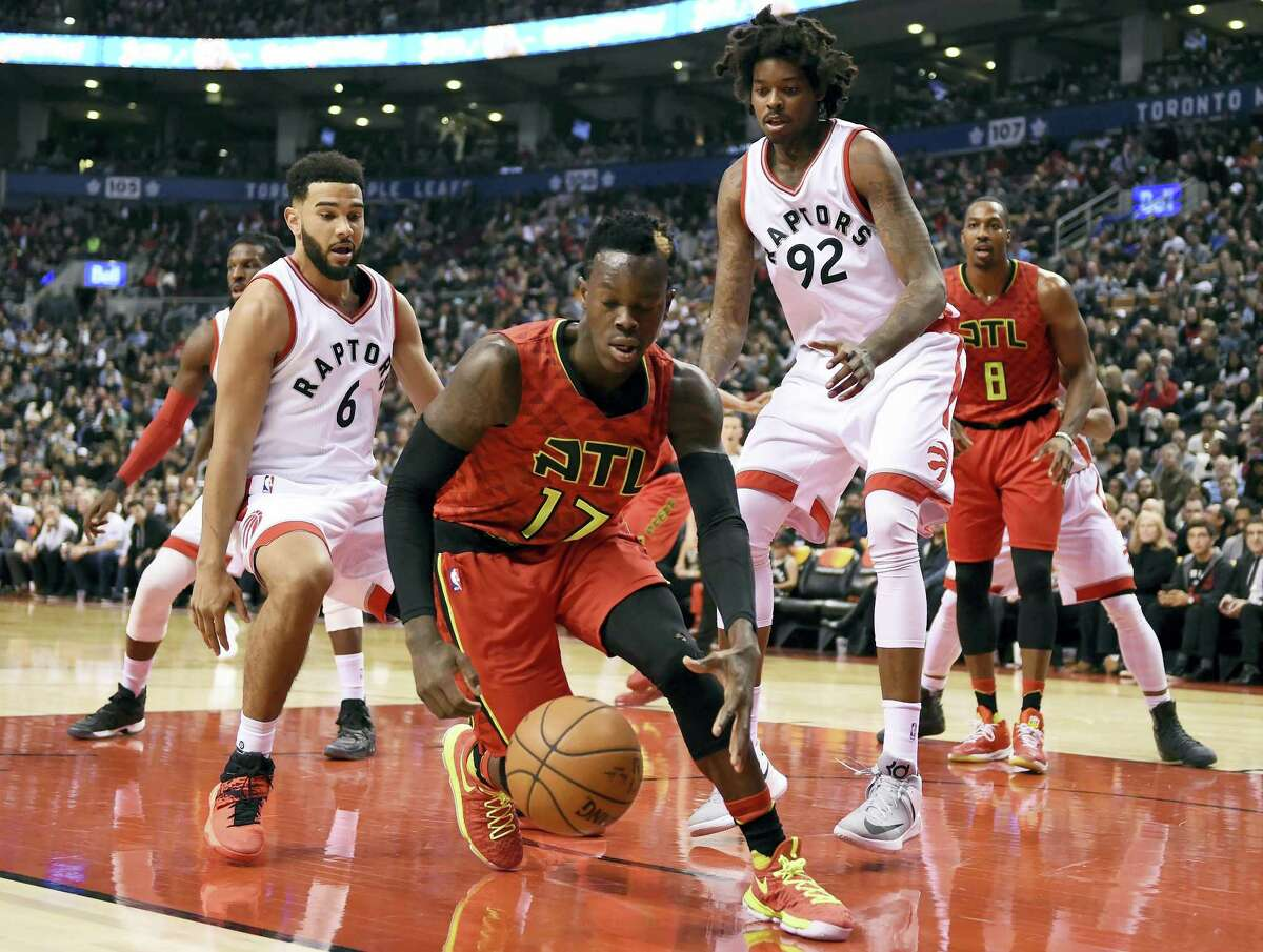 Atlanta Hawks guard Dennis Schroder (17) chases a loose ball as Toronto Raptors guard Cory Joseph (6) and center Lucas Nogueira (92) watch during the first half of an NBA basketball game Saturday, Dec. 3, 2016 in Toronto.