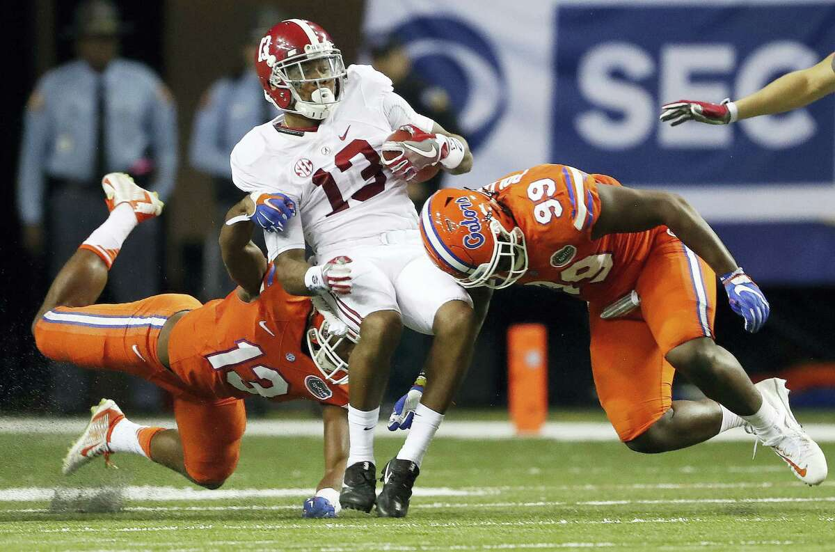 Alabama wide receiver ArDarius Stewart (13) is hit by Florida defensive lineman Jachai Polite (99) and Florida linebacker Daniel McMillian (13) during the second half of the Southeastern Conference championship.