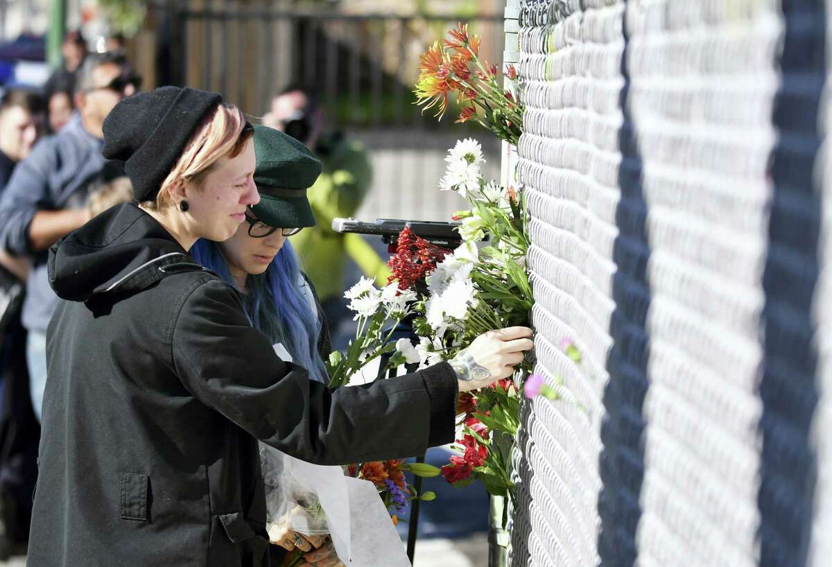 People place flowers near the scene of a warehouse fire Saturday, Dec. 3, 2016 in Oakland, Calif. A deadly fire broke out during a rave at the converted warehouse in the San Francisco Bay Area.