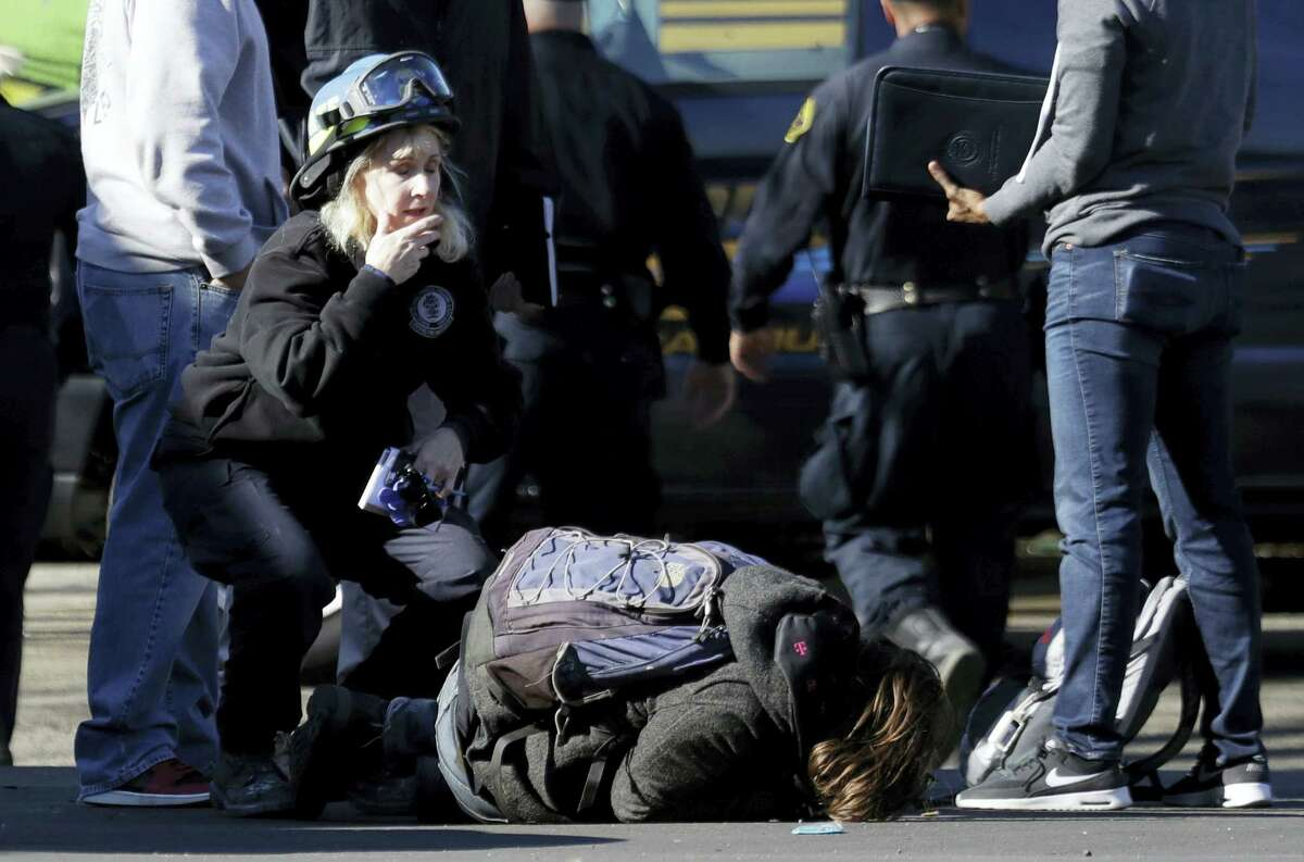 A unidentified man falls to the ground after speaking to authorities outside of a warehouse destroyed by a fire Saturday, Dec. 3, 2016, in Oakland, Calif. A deadly fire broke out during a rave at a converted warehouse in the San Francisco Bay Area. (AP Photo/Marcio Jose Sanchez)