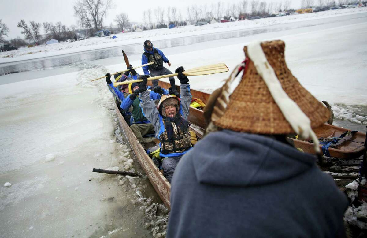 In this Thursday, Dec. 1, 2016 photo, Virginia Redstar of Colville, Wash., and a member of the Colville Native American tribe, celebrates upon reaching shore by canoe at the Oceti Sakowin camp where people have gathered to protest the Dakota Access oil pipeline in Cannon Ball, N.D. Redstar traveled from Montana with fellow tribal members on canoe for 10 days down the Missouri river to reach the camp.