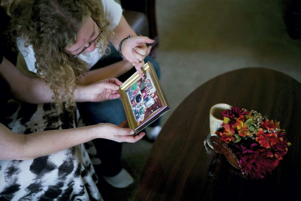 "In this Nov. 21, 2016, photo, Kate Bowman, top, and mother, Karen Fagan, look at an old family photo showing Kate's father and Fagan's ex-husband, Harry Bowman, in Upland, Calif. Bowman was killed in the Dec. 2, 2015, terror attack at the Inland Regional Center in San Bernardino, Calif. ""What angered me most after Dec. 2 was the amount of hate speech going on,"" Bowman said, recalling the day her father and 13 others were killed by husband-and-wife assailants at a lunch meeting for county health inspectors."