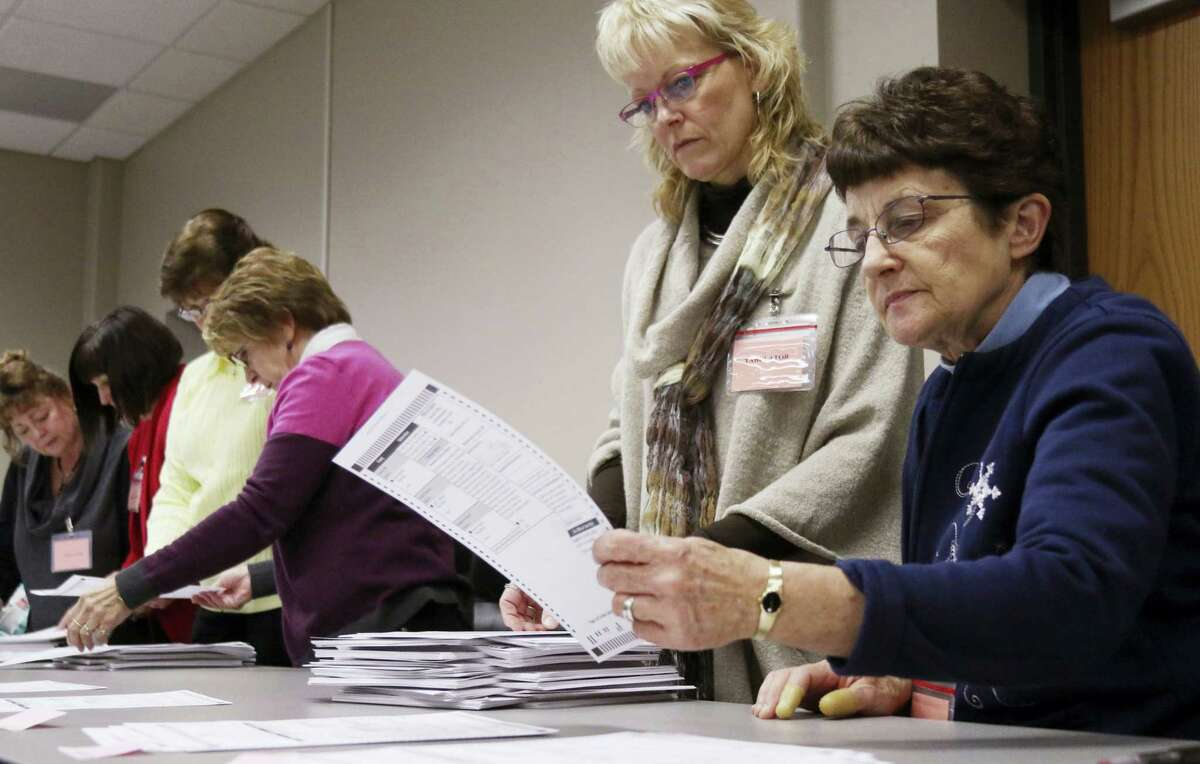 Tabulator Claudette Moll, right, from Farmington, looks over a ballot during a statewide presidential election recount Thursday, Dec. 1, 2016, West Bend, Wis.