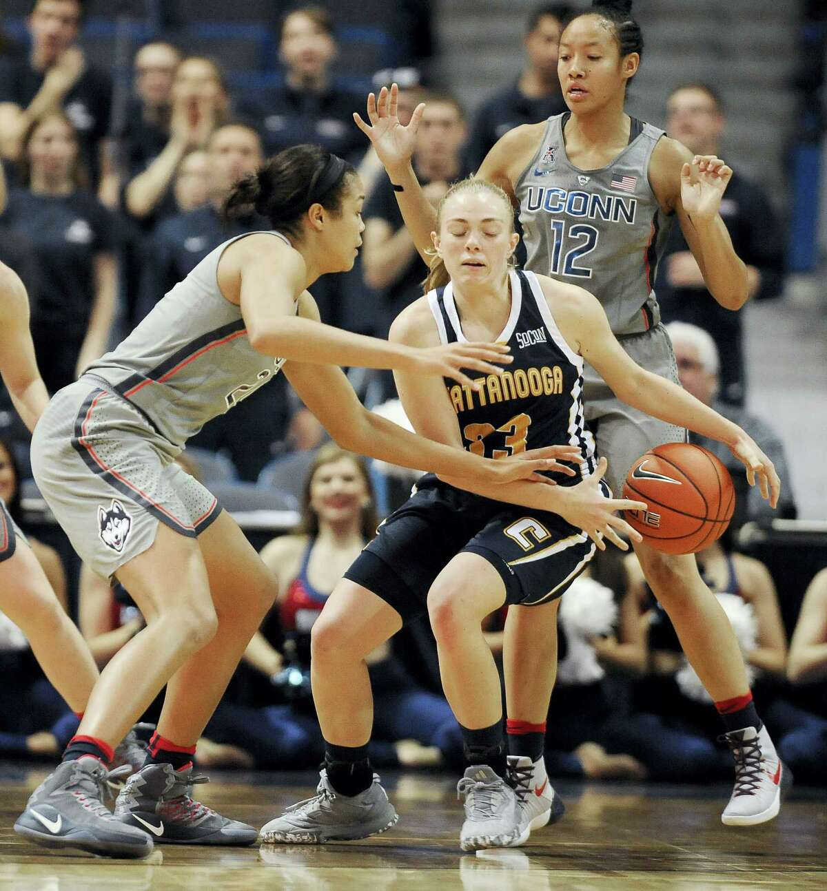 Chattanooga's Lakelyn Bouldin, center, looses the ball under pressure from Connecticut's Napheesa Collier, left, and Saniya Chong, right, in the second half of an NCAA college basketball game, Tuesday, Nov. 29, 2016, in Hartford, Conn. (AP Photo/Jessica Hill)