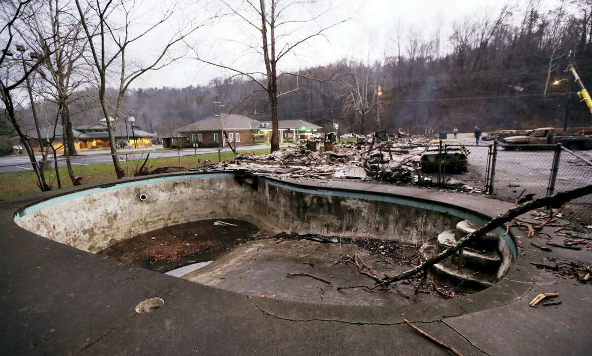AP Photo/Mark Humphrey A swimming pool in a motel complex shows burn marks Wednesday, Nov. 30, 2016, in Gatlinburg, Tenn., after a wildfire swept through the area Monday. Three more bodies were found in the ruins of wildfires that torched hundreds of homes and businesses in the Great Smoky Mountains area, officials said Wednesday.