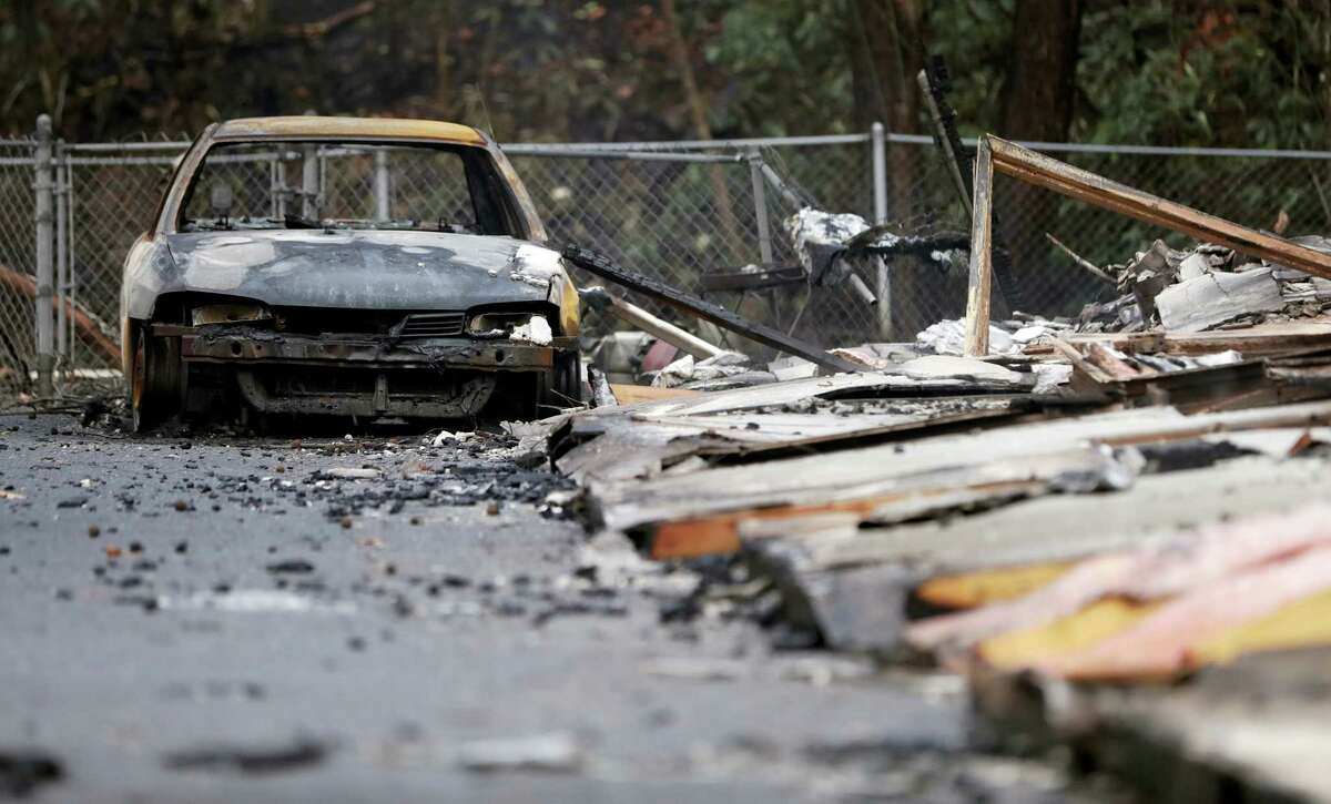 A burned car sits in a parking lot Wednesday, Nov. 30, 2016, in Gatlinburg, Tenn., after a wildfire swept through the area Monday. Three more bodies were found in the ruins of wildfires that torched hundreds of homes and businesses in the Great Smoky Mountains area, officials said Wednesday.