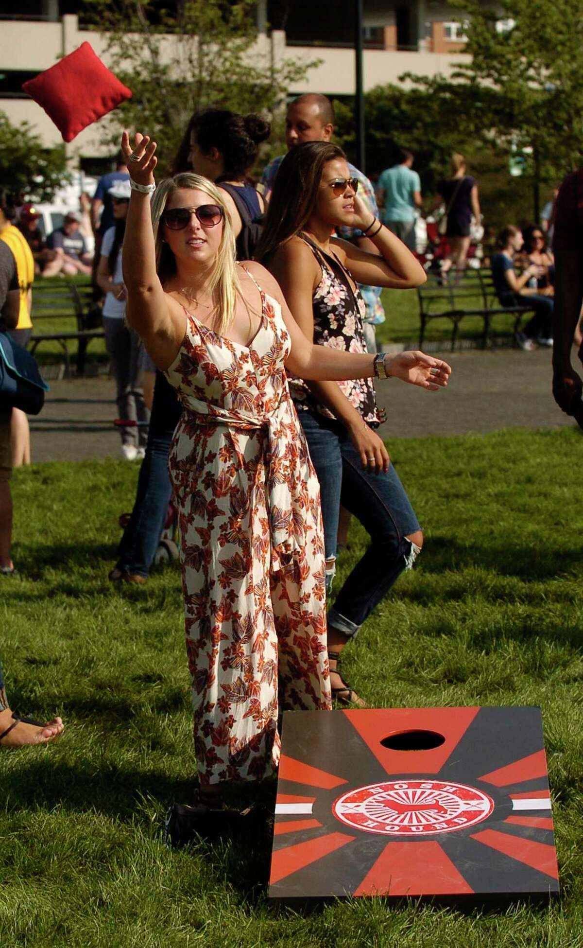 Emily Weiner of Stamford tosses a bean bag as she plays a round of Cornhole with friends during the Hey Stamford Food Fest at Mill River Park in Stamford, Connecticut on Saturday, August 25, 2017.