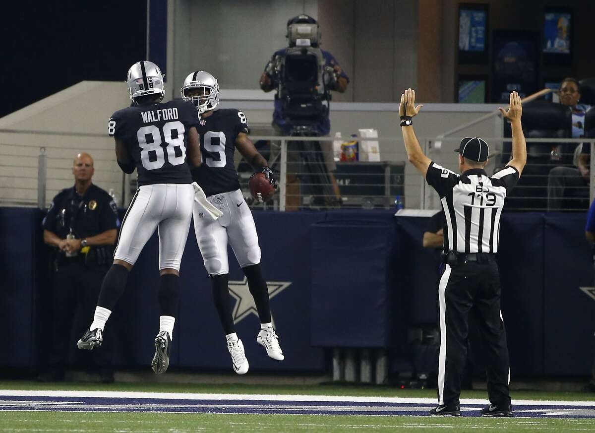Oakland Raiders' Clive Walford (88) and Amari Cooper (89) celebrate a touchdown catch by Cooper as back judge Greg Wilson (119) signals after the play in the first half of a preseason NFL football game against the Dallas Cowboys on Saturday, Aug. 26, 2017, in Arlington, Texas. (AP Photo/Ron Jenkins)