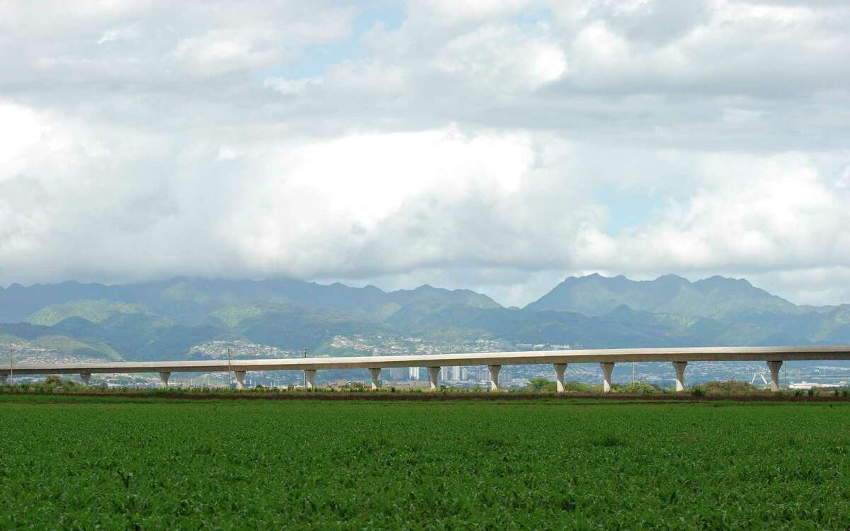 In this May 18, 2017 photo, a rail line under construction passes through farmland in Kapolei, Hawaii. Honolulu's planned $9.5 billion rail transit project is one of the most expensive per capita in the nation. But it's facing a multi-billion dollar budget shortfall, and the future of the project is in jeopardy. Hawaii lawmakers are meeting this week to decide how to cover a budget shortfall as high as $3 billion. (AP Photo/Cathy Bussewitz) ORG XMIT: FX403