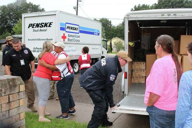 Patton Village Mayor Leah Tarrant hugs a Red Cross volunteer while Police Chief Shannon Sharp lowers the gate of the Red Cross truck on Saturday. Tarrant said that Sharp is responsible for getting emergency services to the Patton Village community in advance of Hurricane Harvey, which is projected to cause some flooding in the area on Sunday or Monday.