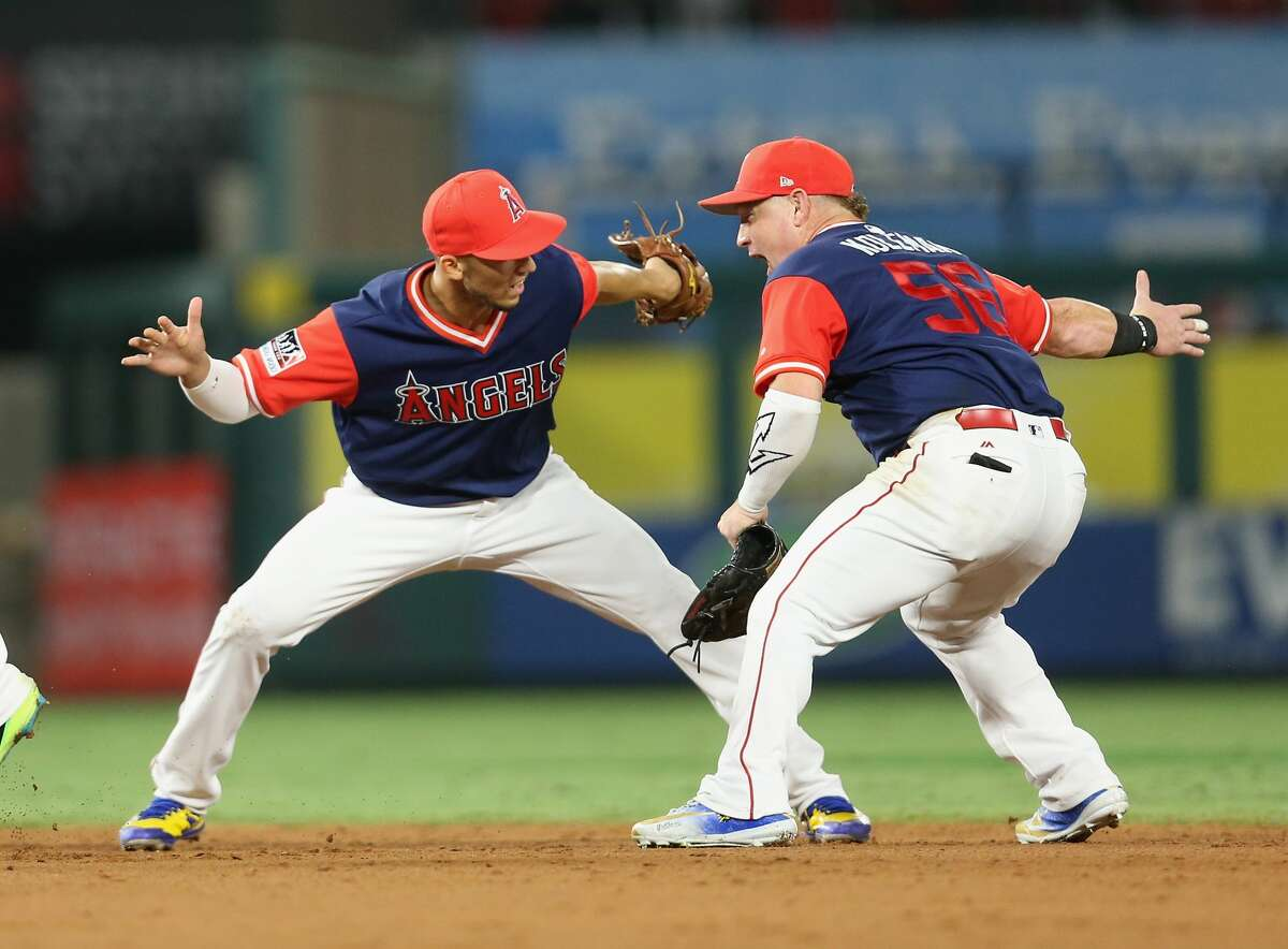 ANAHEIM, CA - AUGUST 26: Andrelton Simmons #2 (L) and Kole Calhoun #56 of the Los Angeles Angels of Anaheim celebrate after the final out of the game against the Houston Astros on August 26, 2017 at Angel Stadium of Anaheim in Anaheim, California. The Angels won 7-6. (Photo by Stephen Dunn/Getty Images)