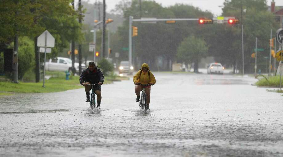 People ride their bikes through the floodwaters on Studewood in the Heights during Harvey. Photo: Karen Warren, Houston Chronicle / @ 2017 Houston Chronicle