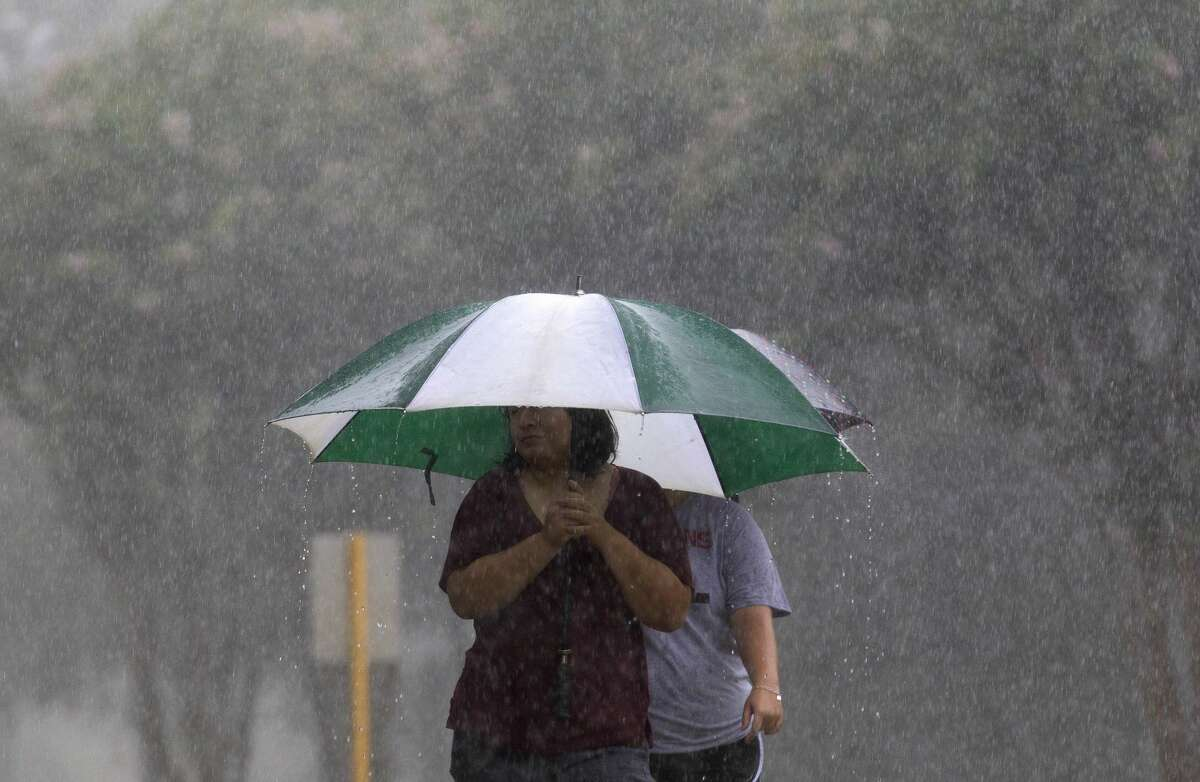 Kingwood residents walk through heavy rain from Tropical Storm Harvey on Sunday.