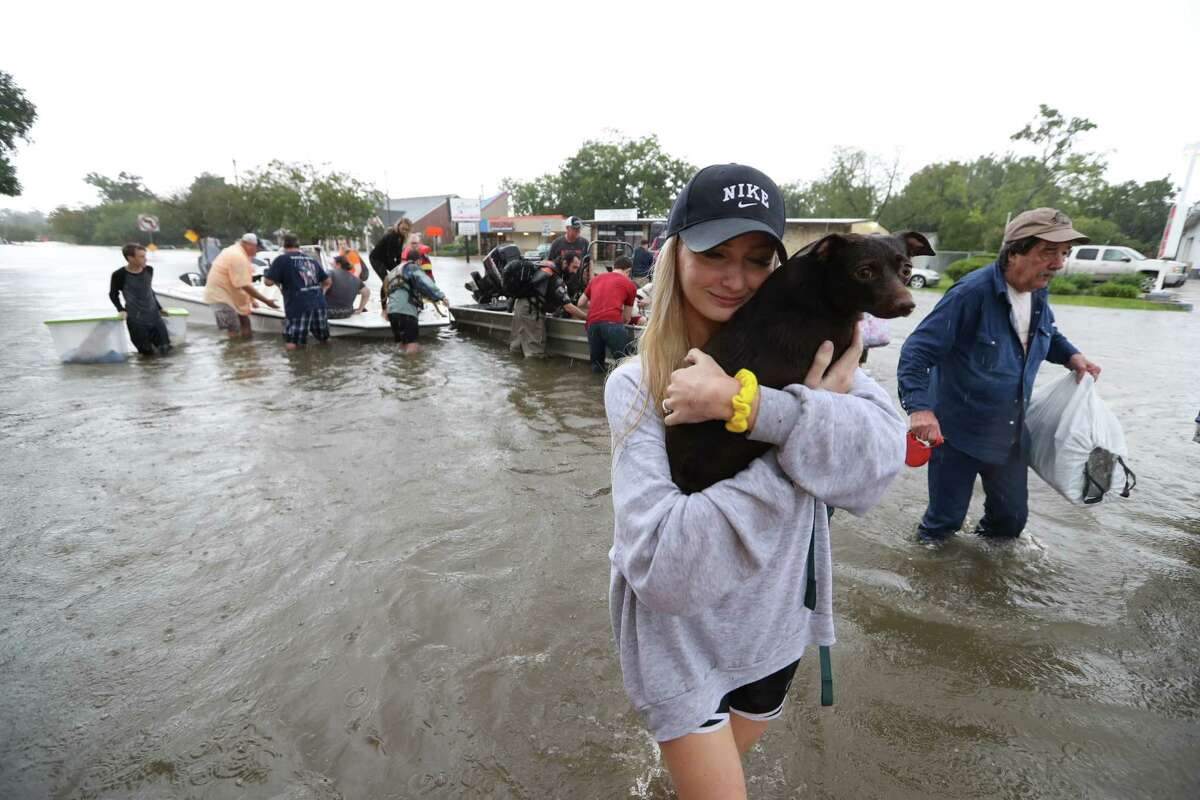 """Photos: Tropical Storm Harvey hammers Houston area Mikhail Bachynsky hugs """"Lily"""" after they were rescued from their home Sunday, Aug. 27, 2017, in Friendswood. Neighbors with boats are using their personal boats to rescue Friendswood residents near FM 2351 and FM 518. See more images from the impact of Tropical Storm Harvey."""