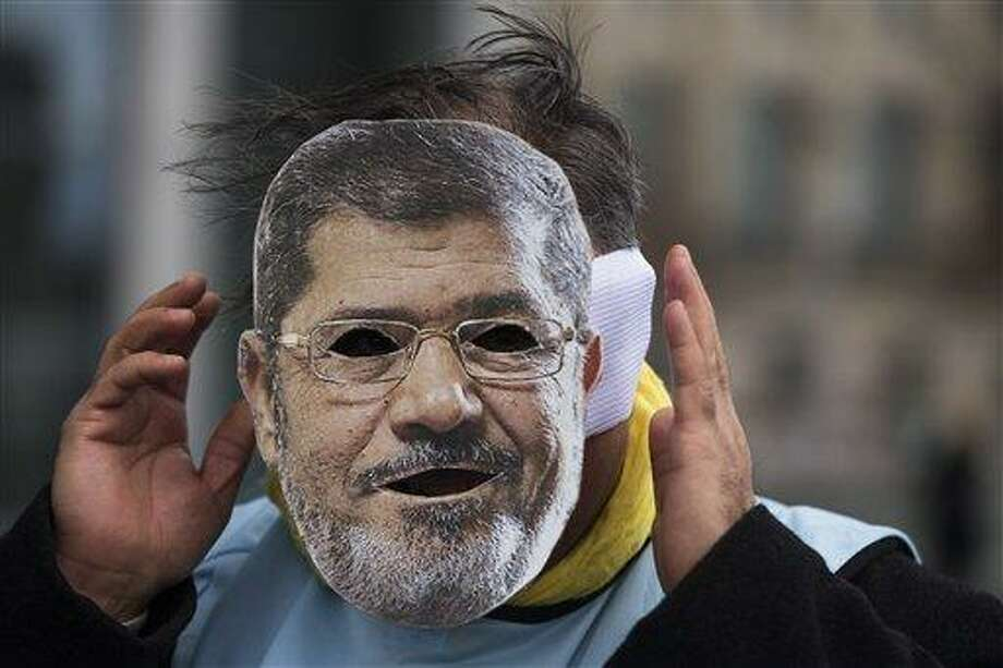 A man covers his face with a mask of Egypt President Mohammed Morsi during a protest in front of the chancellery against the visit of Morsi prior to a meeting of him with German Chancellor Angela Merkel in Berlin, Germany, Wednesday, Jan. 30, 2013. (AP Photo/Markus Schreiber) Photo: AP / AP